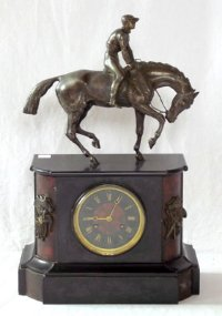 Lot 381: Fine 19th Century Jean-Baptiste Delettrez (1816-87) Paris. 'Horse Racing' Black Slate and Marble Mantel Clock.  Mounted with a wonderful French solid Bronze Horse and Jockey Statue. Below the  Black and Red Marblel Dial,flanked either side with Bronze Horse Motifs. The eight day movement which strikes the hours and half hours on a bell. Movement and pendulum marked JBD. Working complete with key. Possibly commissioned for a racing event or prize.