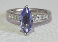 Lot 288 Platinum Tanzanite and Diamond Ring Having Marquise Shape Tanzanite approx 1.05ct with 10 Princess Cut Diamonds to the Shoulders.  Size K. Hallmarked Platinum. Boxed.