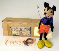 "Lot 403: Rare Mickey Mouse ""Jazzer"" by Dean's Rag Book Company Ltd. London. Circa 1930s. Having  a wire attachment to reverse and is designed to be mounted to a record player so that ""When The Record is Revolving at its Normal Speed the Figure Should Dance an Amazing Variety of Jazz Steps."" Original box, w/label. Mounting Clip and Instructions. Height 18 cm."