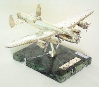 Lot 353: Scarce Silver Lancaster Bomber by Ammonite. Circa 1980.  Hallmarked Birmingham. Mounted on green marble base with silver plaque 'The Lancaster Bomber'.  Height 12cm. Wingspan 32.7cm