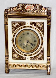 Scarce Wedgwood Queen's Ware Mantel Clock. England, late 19th century. The rectangular case decorated with iron red, black, and gold floral and foliate designs. French 8 day movement striking on a gong.Working order with pendulum and key. Height 12 inches.