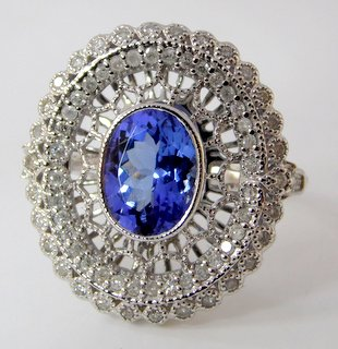 Fine18ct White Gold Tanzanite and Diamond Dress Ring. The 1.42 ct. oval cut tanzanite  highlighted with a pierced and diamond encrusted border with 70 brilliant cut diamonds.0.31 ct. Marked .750.  Size K (11). Boxed
