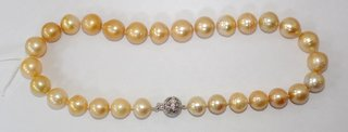 Fine Strand of Golden South Sea Pearls with14 ct White Gold/Diamond Clasp. Consisting of 33 pearls graduating in size,knotted and attached to 14ct white gold filagree ball clasp and pin set  mounted with 4 round brilliant cut melee diamonds. Marked 14K. Length 17.5 inches. Pearls 11.80 to 13.70 mm. Associated box with COA /Value.