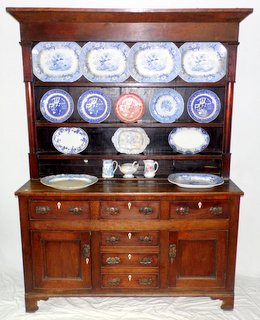 Period Oak North Wales Dresser & China. Late 18th Century. The rack with plain cornice and freeze supported either side by turned pillars with 3 shelves over the base having three drawers along the top with a central drawer and 2 dummies flanked either side by panelled doors all supported on bracket feet. Also included is all the china. Height 85 in. Width 62 in.Depth 19in.