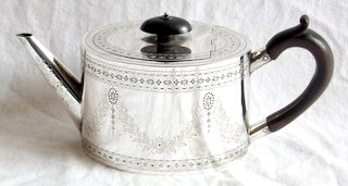 A Victorian Sterling Silver Teapot  by Rupert Favell. Of oval form,straight tapering spout hardwood scroll handle,flush fitting cover button finial, bright cut engraved borders and swags throughout. Hallmarked London 1879. Height 10.5 cm.  Gross weight 11.02 ozs.