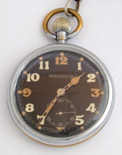 A Jaeger Le Coultre Chrome Plated Open Faced Military Pocket Watch GS/TP XX, P13190, 1950s. Having black dial white arabic numerals and luminous quarters,outer 5 minute divisions and luminous dots.Subsidiary dial for running seconds steel skeleton hands,plain case with snap on front and black broad arrow engraved on the back. Dial signed with leather strap and T piece.