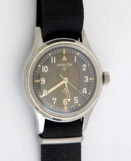 A Rare Hamilton T.6.B Mark II RAF Pilots Military Issue Manual Wrist Watch. Having black dial white arabic numerals and luminous quarters outer 5 minute divisions and luminous dots steel skeleton hands,seconds hand. Plain case the back engraved broad arrow 6B-9101000 H 2614 MI, Dial Signed with strap.