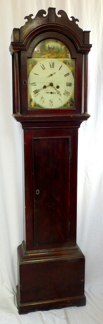 An Early 19th Century Mahogany Longcase Clock by Hardeman of Canterbury, Kent. The 12ins arched painted metal dial with Roman numerals and with subsidiary seconds dial and date dial, the arch and spandrels painted with cottages to the eight day two train movement striking on a bell, Going order with weights and pendulum.  Height 76 inches.