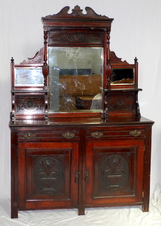 Victorian Carved Walnut Mirror Back Sideboard. Late 19th Century. The carved pediment over a large central bevelled mirror flanked either side by further mirrors and shelves. Below 2 storage drawers over a 2 door cupboard all supported on style legs,  Height 80 in.  Width 53 in. Depth 18 in.