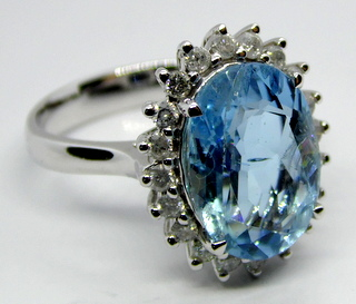 l4ct White Gold Aquamarine and Diamond Ring. Featuring  Central Oval Cut Aquamarine (3.16 ct) with 20 Round Brilliant Cut White Diamonds (0.34 ct). Size K(11). Marked 14K. GGVS Certificate. Boxed
